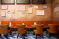 Vintage style, interior of a cafe, wall with empty frames, leather armchairs.