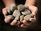Man holding different small rocks in his hands