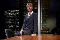 Business woman sitting at table in boardroom looking at camera