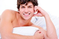 Attractive sexy smiling young nude man lying in bed with pillow