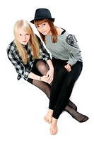Two beautiful young girls sit on floor