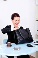 Pretty caucasian businesswoman searching in her black bag at the desk in the office.