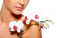 Beauty flower lying on nude female shoulder with clean healthy skin