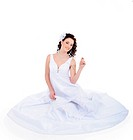 Attractive young bride sitting on floor dressed on white wedding dress