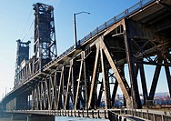 Old rusty steel bridge that carries rail and road traffic in Portland OR