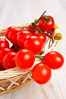 Red cherry tomatoes on a branch in wicker basket