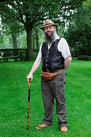 Proud vintage real estate owner or yeoman with cane in his park.
