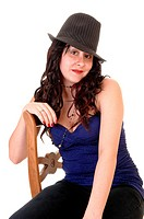 Woman sitting on a chair in a blue top and with long curly black hair anda gray hat, for white background.