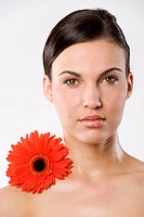 fresh portrait of a young brunette woman wiith color flower without skin retouch