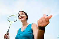 Pretty, young woman playing badminton in a city park on a lovely summer day shallow DOF