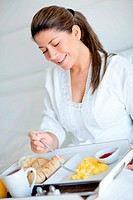 Woman enjoying room service and eating breakfast at a hotel
