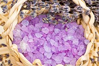Aromatic bath salt and dry lavender flowers in wicker basket shallow DOF
