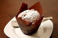 A picture of a chocolate muffin covered with icing sugar and served on a white plate