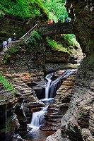 Waterfall with bridge and hiking trail in woods with rocks and stream in Watkins Glen state park in New York State
