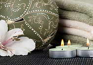 Spa concept with candle, towel and by the white Alstroemeria