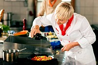 Two chefs in teamwork _ man and woman _ in a restaurant or hotel kitchen cooking delicious food in professional manner