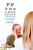Elderly woman choosing a pair of glasses at the optician
