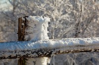 Snow blown into sharp shapes on old wooden fence post