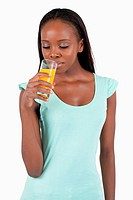 Young woman looking into her glass of orange juice against a white background