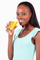 Side view of smiling woman with orange juice against a white background