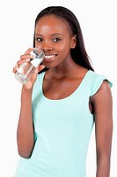 Happy smiling woman having a glass of water against a white background