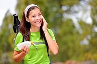 Hiker sunscreen. Woman hiking putting sun block lotion outdoors during summer hike holidays. Mixed race Caucasian Asian female model.