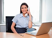 Portrait of smiling businesswoman talking on phone with laptop on her desk