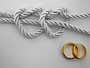 Double heart shaped silver rope tied and a double gold ring