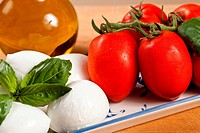 Close up of mozzarella cheese bits and cherry tomatoes with basil leaf and oil bottle ready to make healthy Caprese salad