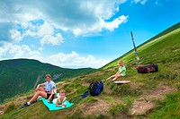 Family resting in a summer mountain walk Goverla Mount, Ukraine