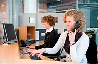 Two professional women working at a front desk.