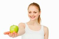 Cheerful woman presenting an apple against white background