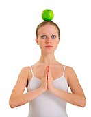 young woman meditating with apple on her head isolated on white background