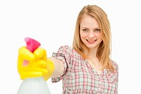 Woman holding a spray bottle while smiling against white background