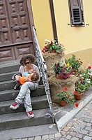 Mother breastfeeding her daughter on a home staircase