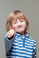 boy with long blond hair showing thumbs up sign, smiling - isolated on gray