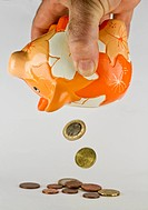 orange piggy bank with falling euro coins