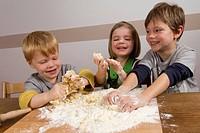 Kids making dough for baking christmas cookies