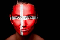 Portrait of a woman with the flag of the Denmark painted on her face.