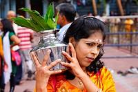 Pilgrim making a milk sacrifice, Hindu festival Thaipusam, Batu Caves limestone caves and temples, Kuala Lumpur, Malaysia, Southeast Asia, Asia