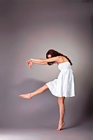 Beautiful young woman in white dress dance with shadow