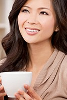 A beautiful young Chinese Asian Oriental woman with a wonderful toothy smile drinking tea or coffee from a white cup