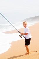 happy little boy fishing on beach