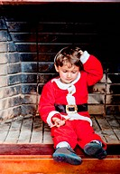Boy dessed up as Santa Claus sitting on the chimney