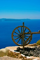 Wooden wheel in Santorini with Aegean sea in the background. Beautiful summer light day.