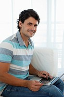 Man holding credit card while using laptop computer, portrait