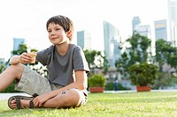 Boy sitting on grass in park, city skyline in background