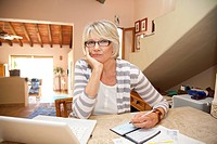 Woman writing checks in home office
