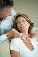 Mature man giving woman a pearl necklace