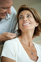 Mature man giving woman necklace